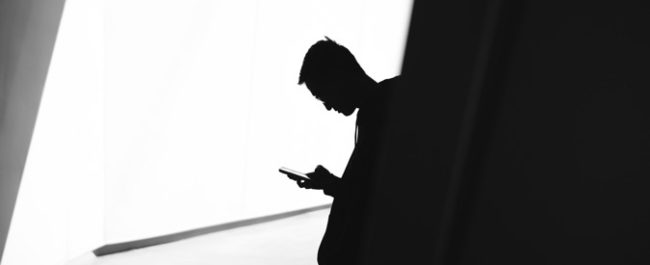 Black and white image and silhouette of man on the phone